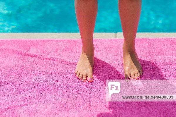 Geschnittene Aufnahme von jungen Frauen Beine und Füße stehen auf rosa Strandtuch am Pool.
