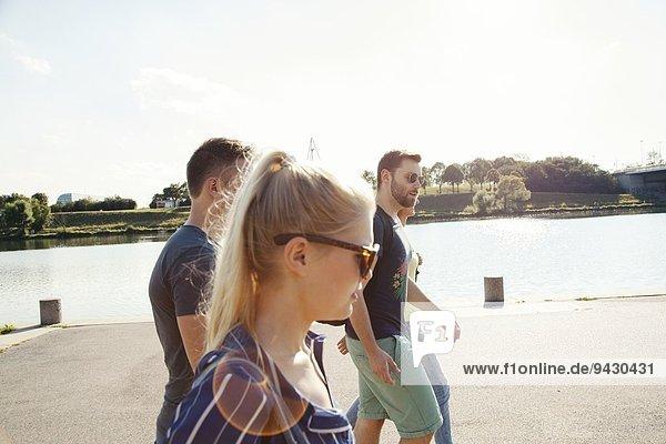 Vier junge Freunde  die am Flussufer spazieren gehen.