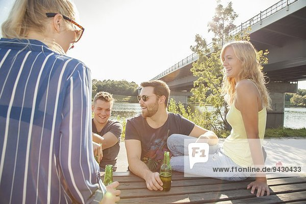 Four young friends drinking beer on riverside picnic bench