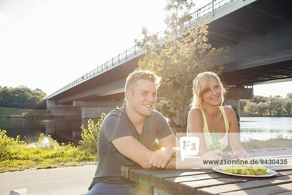 Young couple drinking beer on riverside picnic bench