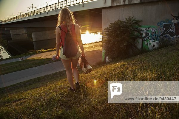 Rear view of young woman walking near bridge and riverside