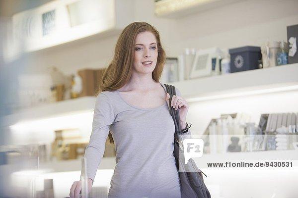 Frau geht an Produkten in den Verkaufsregalen vorbei