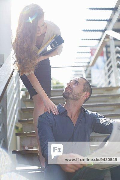 Geschäftsfrau winkt Geschäftsmann auf Treppe
