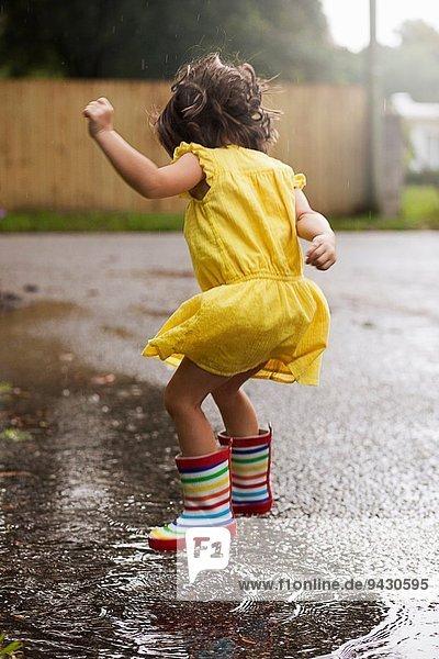 Mädchen in Gummistiefeln springen in Regenpfütze