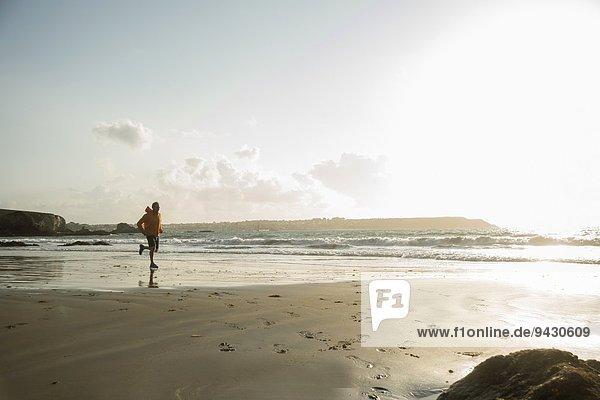 Mature man running on sand  along coastline