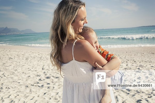 Mid adult mother carrying young son on beach  Cape Town  Western Cape  South Africa