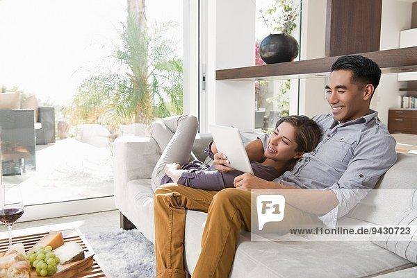 Paar auf dem Wohnzimmersofa mit Blick auf das digitale Tablett