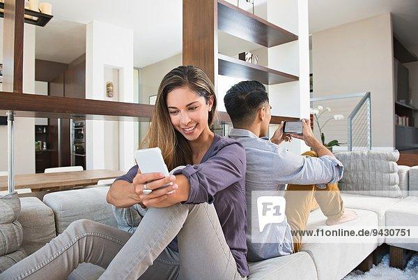 Rücken an Rücken Pärchen beim Spielen auf Smartphones auf dem Wohnzimmersofa
