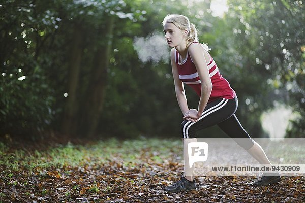 Frau streckt sich im Wald