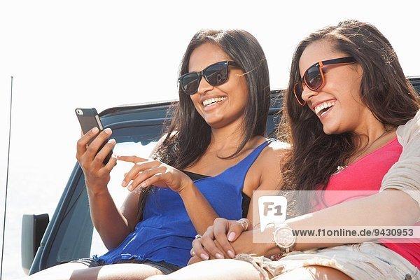 Zwei junge Frauen sitzen auf einer Jeep-Haube und schauen auf das Smartphone.