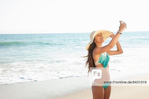 Junge Frau nimmt Selfie auf Smartphone am Strand  Malibu  Kalifornien  USA