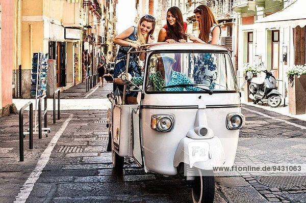 Drei junge Frauen auf dem offenen Rücksitz eines italienischen Taxis  Cagliari  Sardinien  Italien