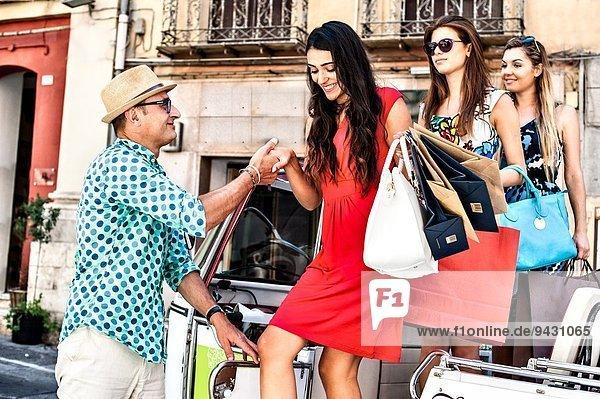 Taxifahrer hilft drei jungen Frauen beim Aussteigen aus dem Taxi  Cagliari  Sardinien  Italien