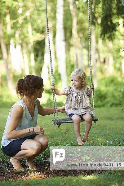 Mittlere erwachsene Mutter und Kleinkind-Tochter beim Spielen auf der Gartenschaukel