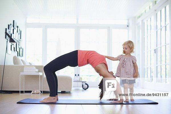 Mittlere erwachsene Mutter praktiziert Yoga mit neugieriger Kleinkind-Tochter