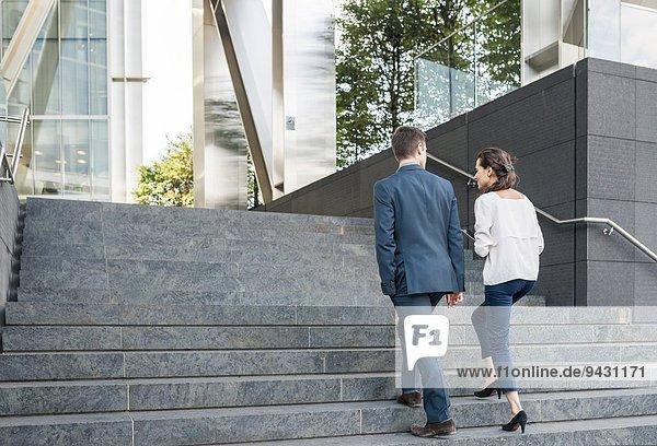 Rückansicht des jungen Geschäftsmannes und der Frau  die die Treppe hinaufgehen  London  UK