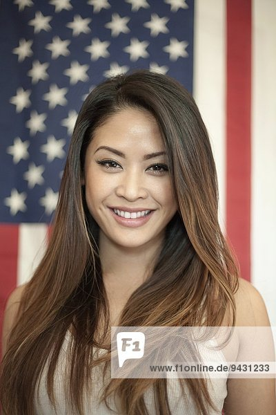 Portrait of young woman standing in front of american flag