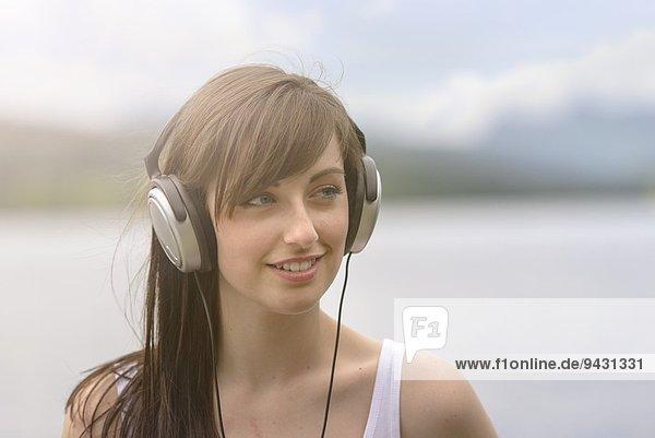 Junge Frau mit Kopfhörer am Seeufer unter hellem Sonnenlicht
