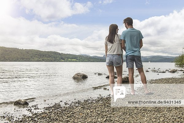 Young couple looking to each other at the edge of lake under sunny sky