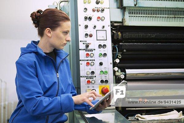 Fabrikarbeiter am Bedienpult der Maschine