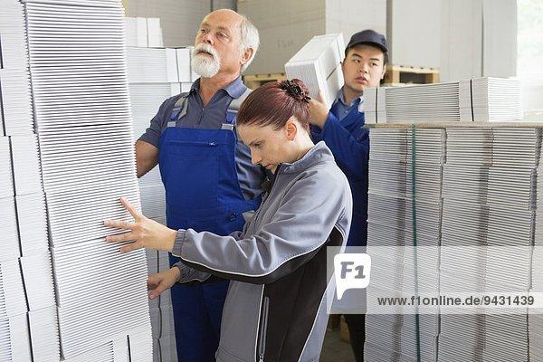 Fabrikarbeiter beim Bewegen und Stapeln von Kartonagen