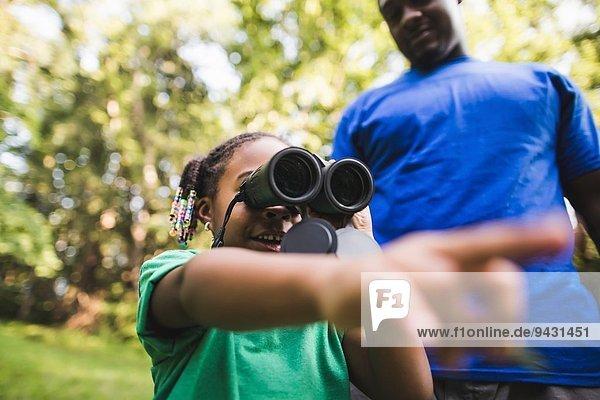 Vater und Tochter schauen durchs Fernglas im Waldökocamp