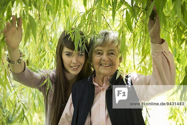 Grandmother and granddaughter under willow tree