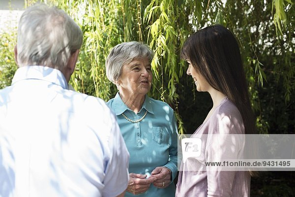 Grandparents and granddaughter having conversation in garden
