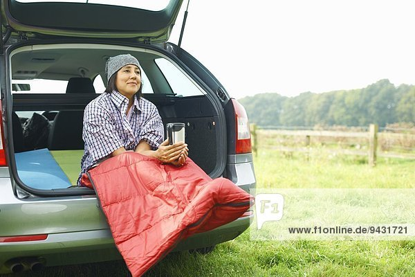 Woman sitting at rear of car with legs tucked in sleeping bag