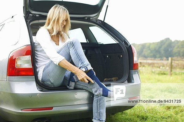 Woman sitting at rear of car putting on socks
