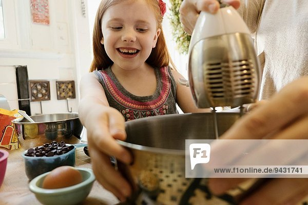 Girl giving mother a helping hand in kitchen