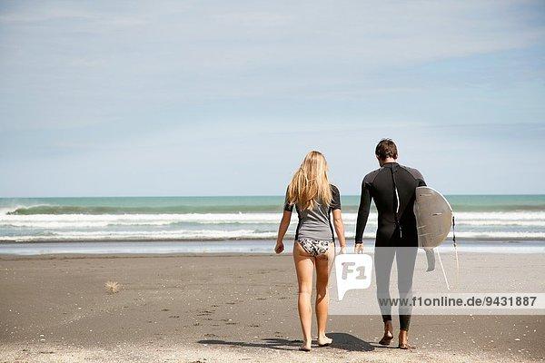Junges Paar  das aufs Meer hinausgeht  junger Mann mit Surfbrett