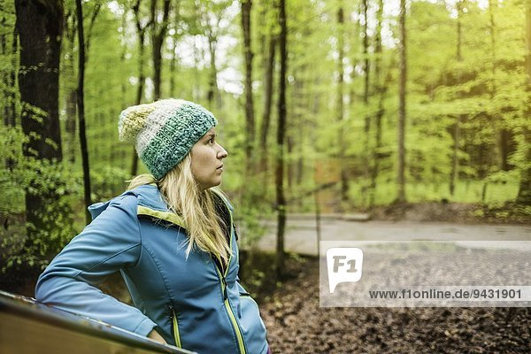 Young woman standing in forest looking away