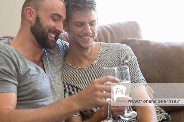 Männliche Paare stoßen sich gegenseitig mit Champagner auf dem Sofa an.