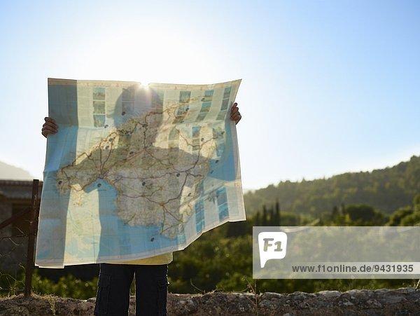 Schatten eines Jungen  der eine Karte hochhält  Mallorca  Spanien