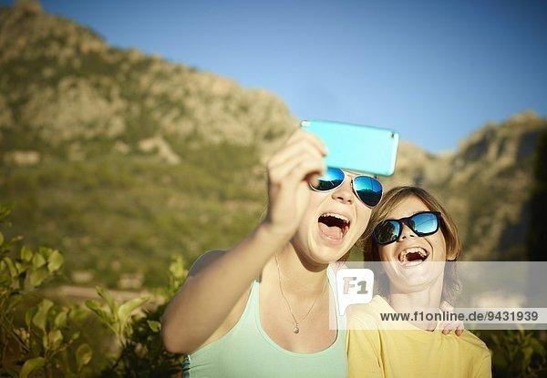 Schwester und Bruder machen Gesichter für Selfie auf Smartphone  Mallorca  Spanien