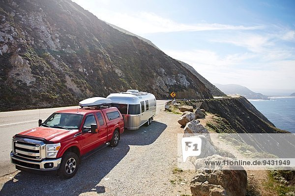 Pick-up truck with trailer attached on mountain road  Big Sur  California  USA