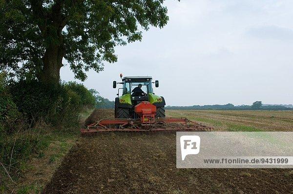 Landwirt fährt Traktor und pflanzt Mais auf dem Feld an