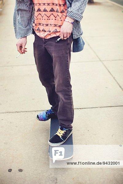 Skateboarder's legs on concrete pavement