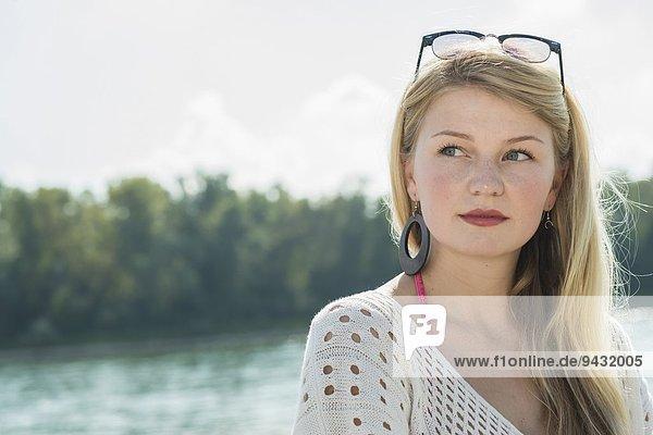 Junge Frau mit langen blonden Haaren schaut weg  Portrait