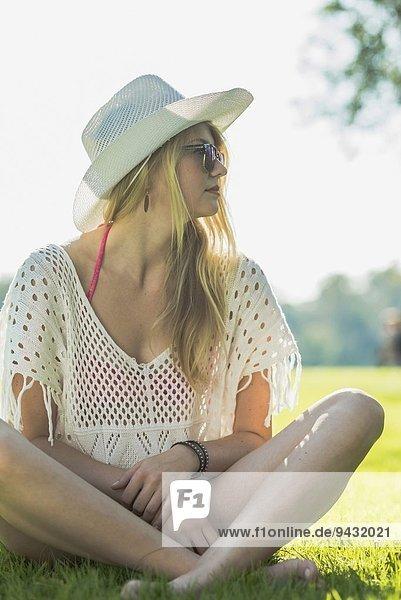 Junge Frau mit weißem Sonnenhut im Kreuzbein sitzend