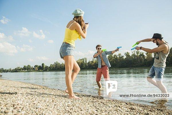 Junge Männer spielen mit Wasserpistolen im See
