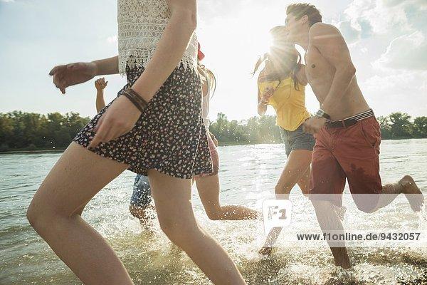 Gruppe junger Freunde beim Laufen im See
