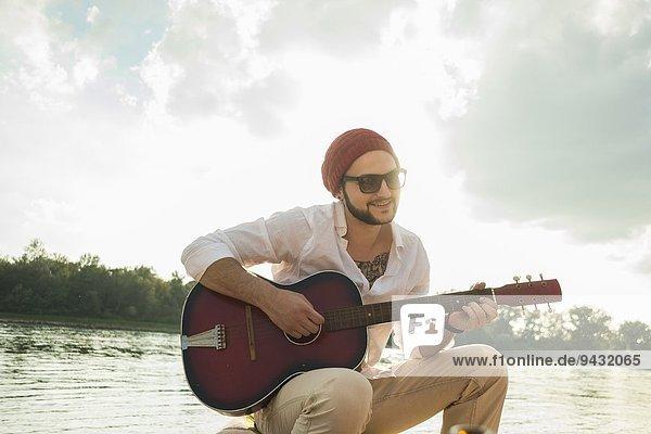 Junger Mann sitzt am See und spielt Gitarre.