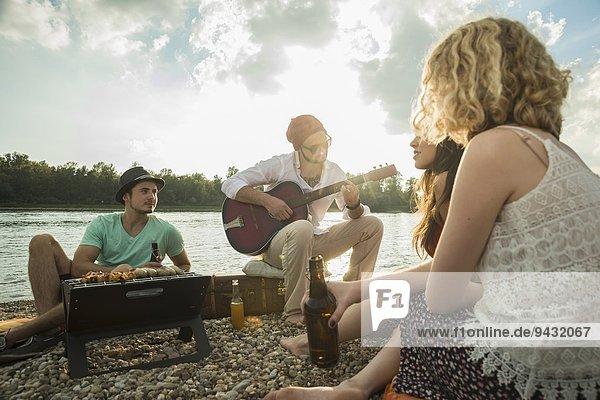 Junger Mann am See mit Freunden beim Gitarrespielen