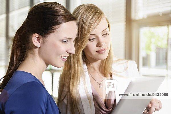 Geschäftsfrauen nutzen digitales Tablett zur Diskussion