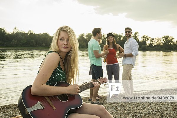 Junge Frau spielt Gitarre am See
