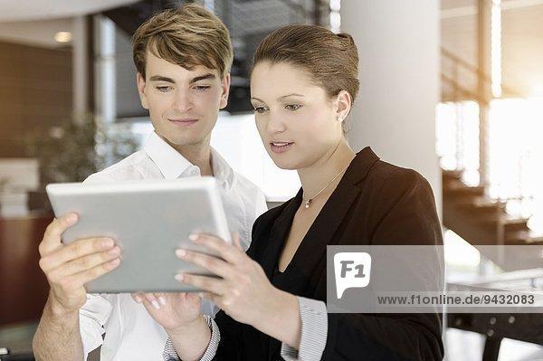 Geschäftsfrau und Geschäftsmann mit digitalem Tablett im Gespräch
