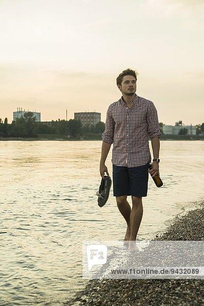 Junger Mann geht mit Schuhen am See entlang
