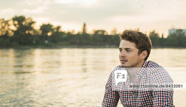 Junger Mann in kariertem Hemd am See